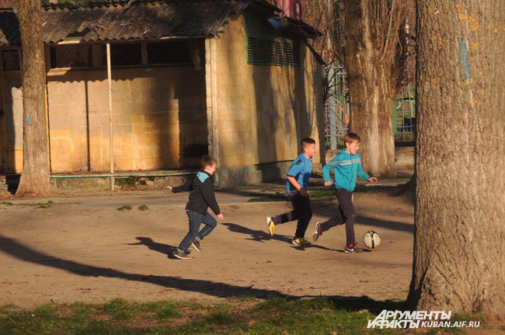 Мальчишки играют в футбол на пляже реки Кубань.