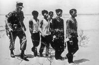Американский военнослужащий конвоирует южновьетнамских пленных, подозреваемых в связях с партизанами. Война в Южном Вьетнаме (ныне Социалистическая Республика Вьетнам).