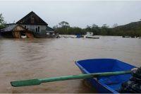 К подтоплённым домам добирались на лодках.