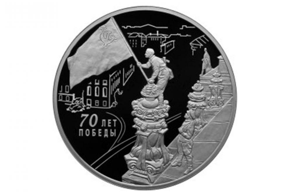 На оборотной стороны трехрублевой монеты – рельефные изображение советских воинов, водружающих Знамя Победы над Рейхстагом.