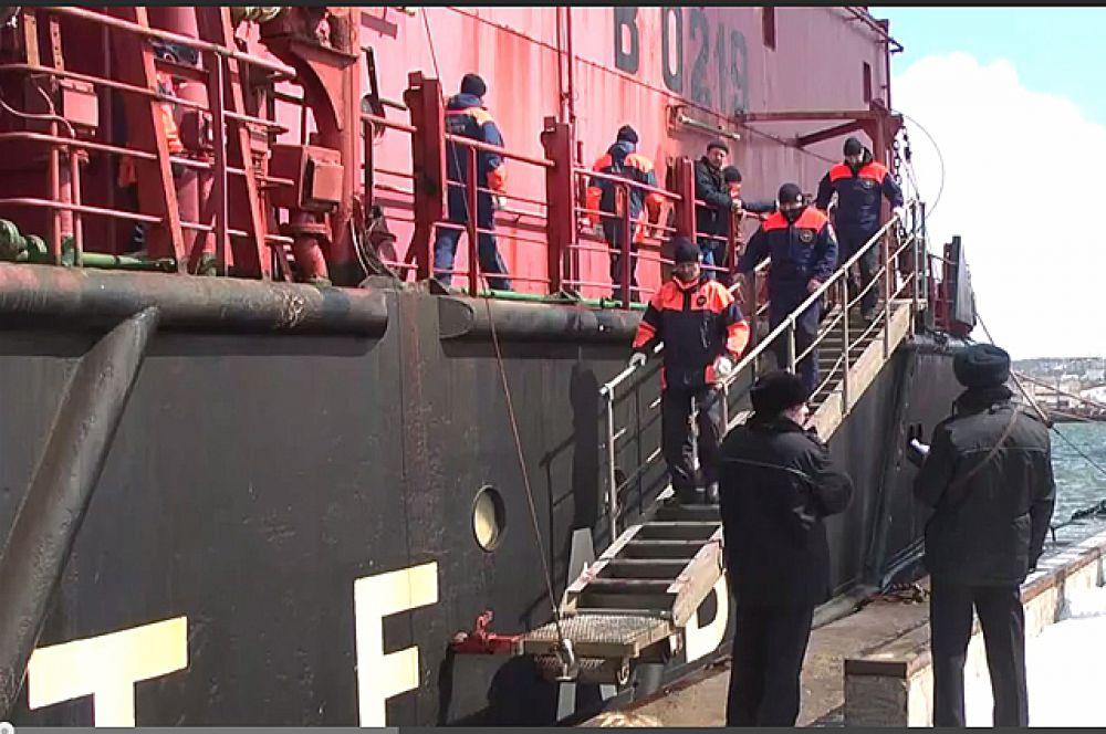 Спасённые члены экипажа спускаются на берег.
