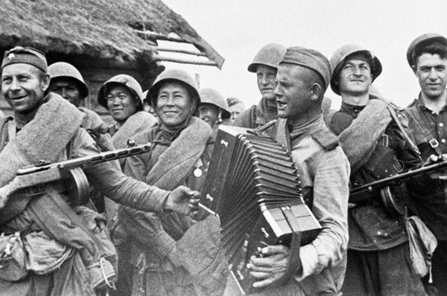 Солдат играет на гармони для своих однополчан.
