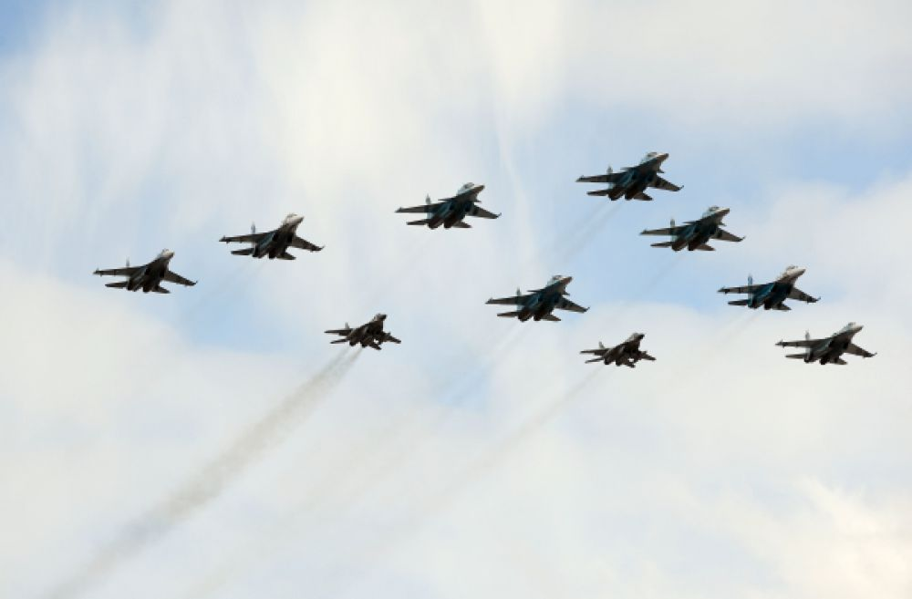 Ударные истребители-бомбардировщики Су-34 и высокоманевренные истребители Су-27, многоцелевые истребители МиГ-29 в небе Подмосковья репетируют траекторию полета для Парада Победы.