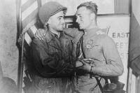 2-й лейтенант У. Робертсон и лейтенант А. С. Сильвашко на фоне надписи «Восток встречается с Западом», символизирующей историческую встречу союзников на Эльбе.