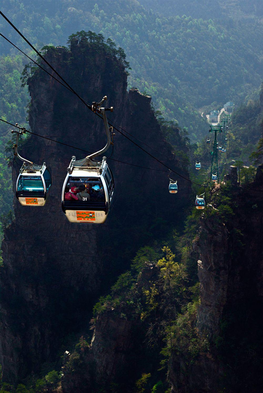 Горы в парке Чжанцзяцзе в Китае настолько высокие, что, кажется, будто они парят в воздухе, тем более что их основание трудно разглядеть в тумане. Именно поэтому канатная дорога посреди скал этого парка считается самой захватывающей в мире. Перепад давления во время подъема здесь такой, что у пассажиров нередко закладывает уши, а температура в кабине понижается. Местную канатку неслучайно называют «дорогой в небеса»: на некоторых отрезках она поднимается вверх под углом 70°, врезаясь прямо в облака. В общей сложности протяженность канатной дороги 7455 метров, а подъем занимает 40 минут.