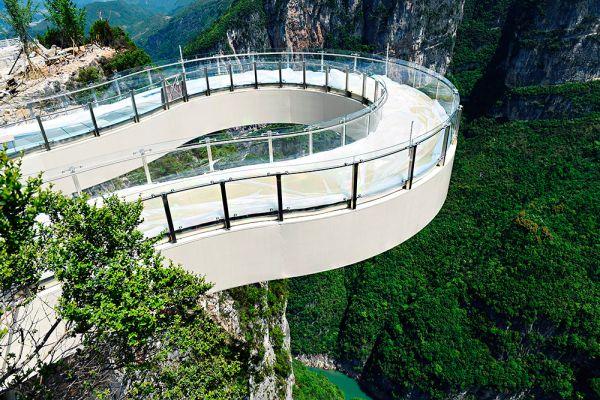 Удивительный мост, который называют самым длинным в мире консольным мостом, был введен в эксплуатацию в геологическом парке Лунган (уезд Юньян, Чунцин, Китай) 26 апреля. Конструкция имеет стеклянный пол и отходит от массива скалы на расстояние 26,68 м. Это более чем на 5 м больше, чем предусмотрено конструкцией аналогичной площадки над Гранд-Каньоном. Необычное сооружение делает петлю над ущельем на высоте 718 м. Конструкция была спроектирована так, чтобы выдерживать землетрясения магнитудой до 8 баллов.