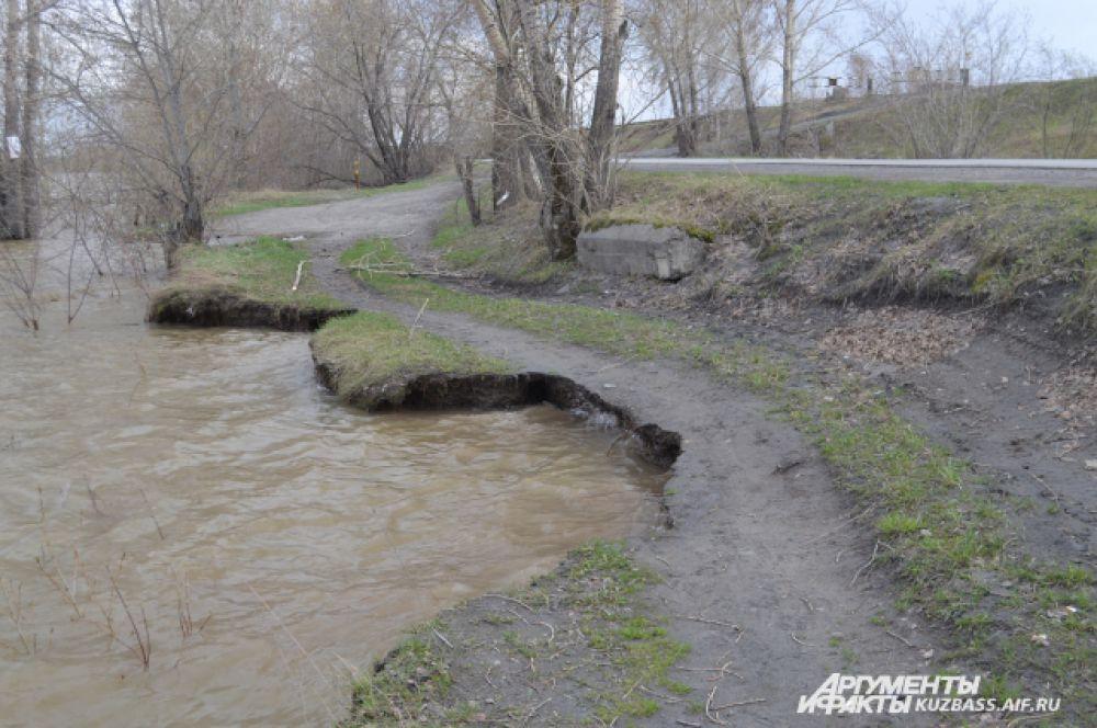 Вода почти вплотную подошла к основанию дороги и размывает его.