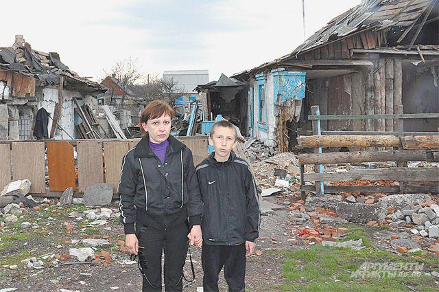 Анна с сыном у руин дома. Её семья чудом осталась в живых.