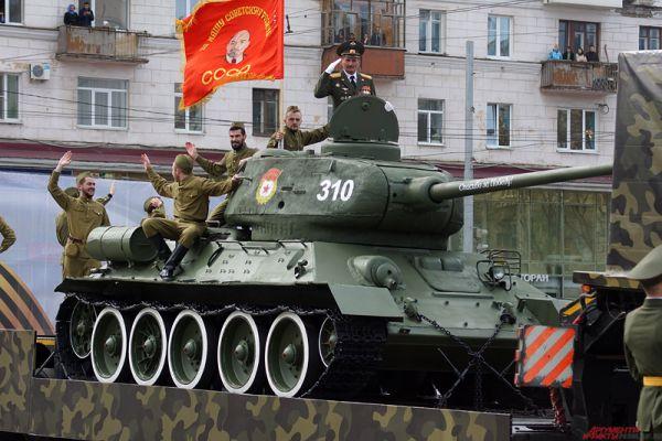 В этом году колонну боевой техники возглавлял легендарный танк Т-34, который принял участие в Великой Отечественной войне в составе 65-го Гвардейского танкового полка. Он участвовал в боях на Западном фронте, в сражениях за освобождение Украины, Польши, одним из первых вошел в пригород Берлина. Членом экипажа был наш земляк из города Оса, старший лейтенант Михаил Саначев.
