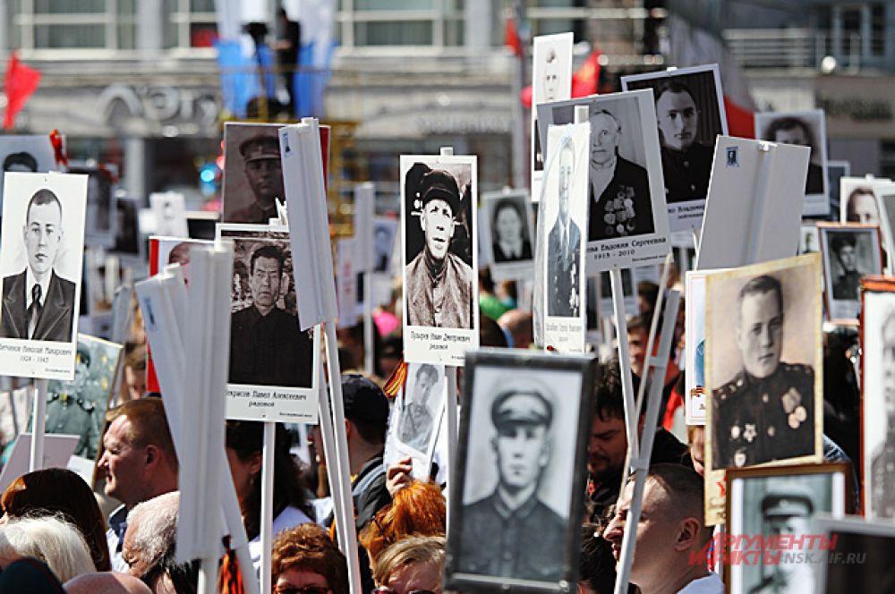 Потомки воинов чтят их память и с гордостью несут в руках их портреты.