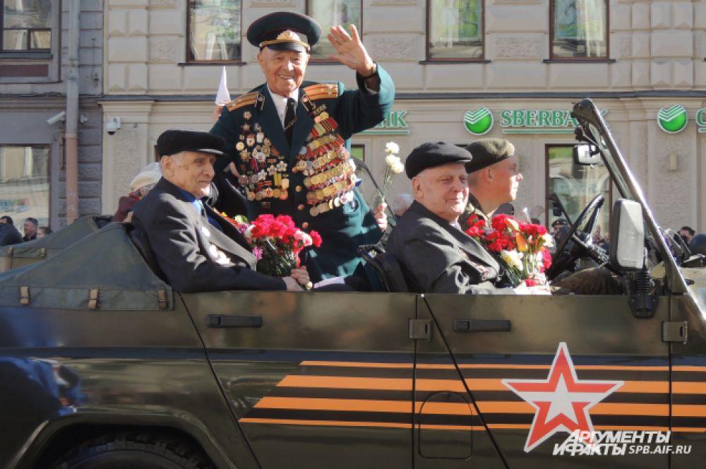 Люди на улицах приветствовали ветеранов.