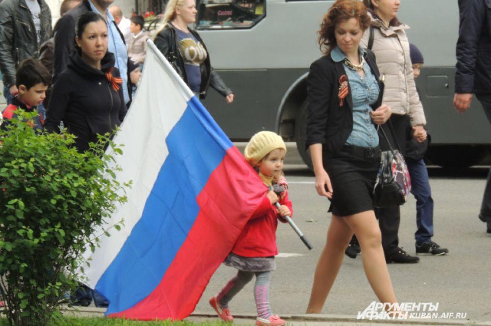 Маленькие дети с  удовольствием и гордостью несут в руках российский флаг.