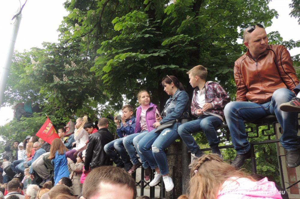 Дети забрались на забор для лучшего обзора.