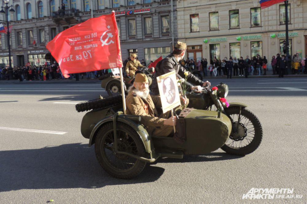 Ветеранов провезли по Невскому проспекту в автомобилях и на мотоциклах.