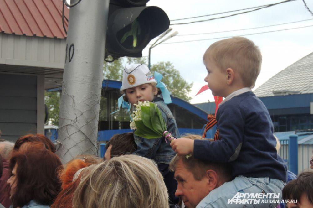 Детей родители сажают на плечи, чтобы они увидели парад.