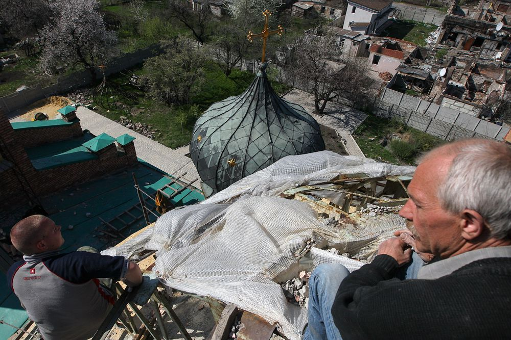 Горожане во время уборки территории храма святителя Игнатия Брянчанинова, пострадавшего в результате боевых действий в аэропорту Донецка.