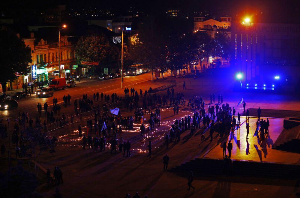 Участники акции почтили память жертв депортации минутой молчания, после чего горящими свечами выложили контур Российской Федерации и национального крымско-татарского символа «Тамга».