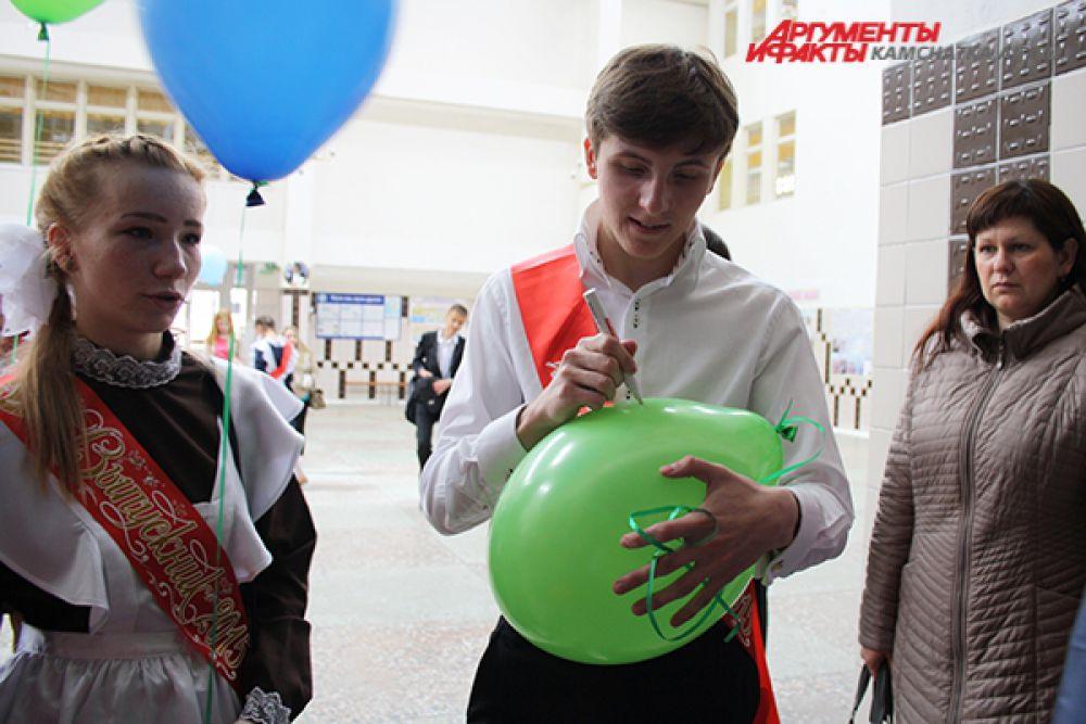 По традиции выпускники пишут свои пожелания на воздушных шарах.