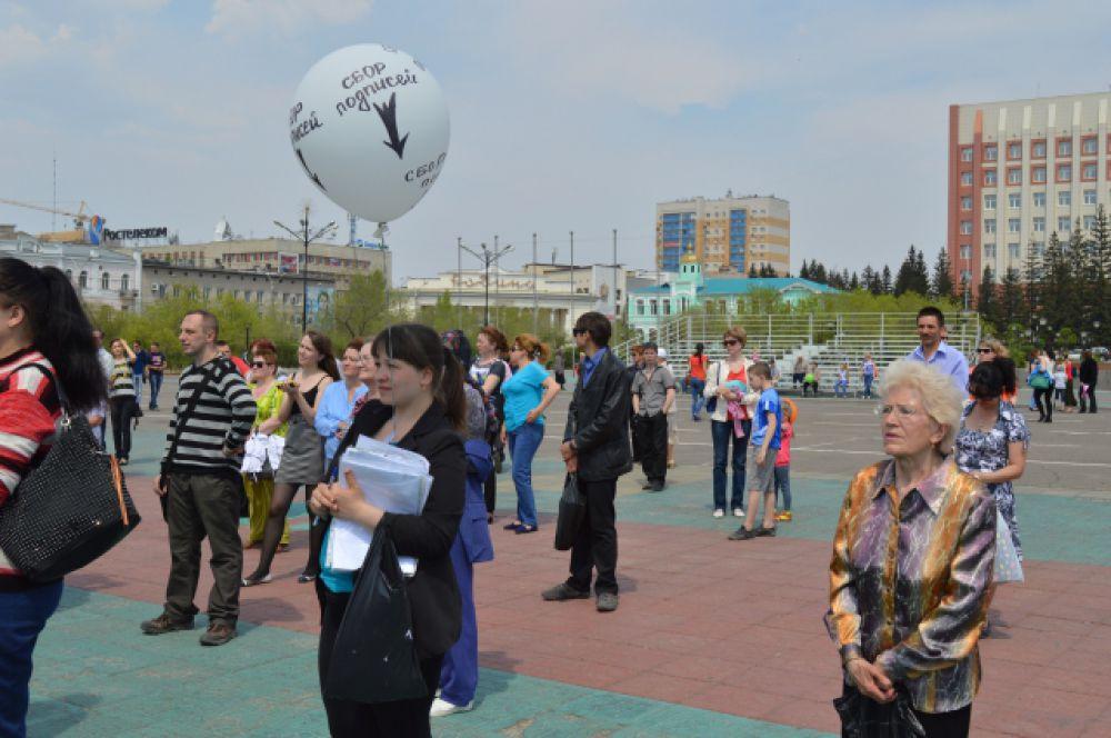 Девушка собирает подписи. Об этом красноречиво говорит надпись на воздушном шарике.