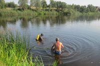 Водолазы ищут тело в воде.