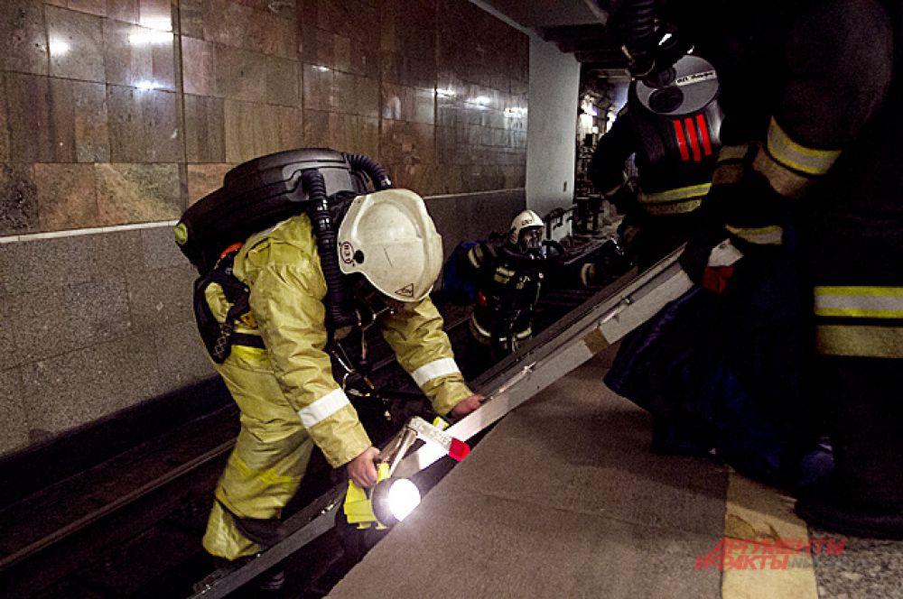 Чтобы потушить пожар в вагоне, спасатели должны спуститься на рельсы.