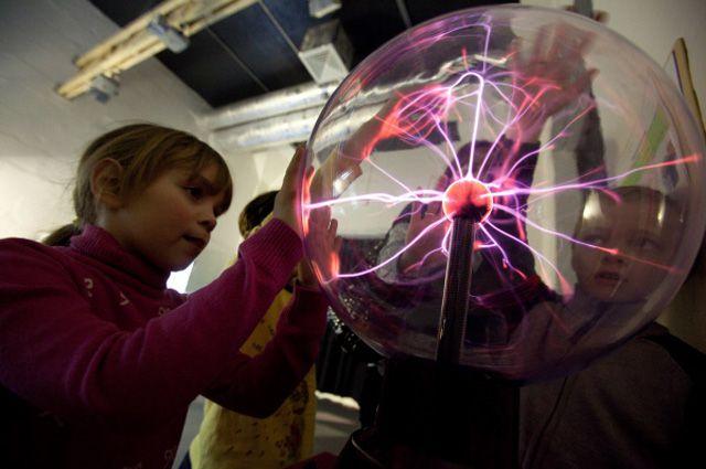 Дети играют с плазменным шаром в музее занимательных наук «Экспериментаниум» в Москве.