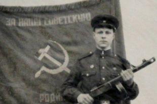 Сержант Олег Анохин на фоне знамени полка.