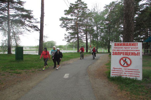 Люди гуляют по велодорожкам.
