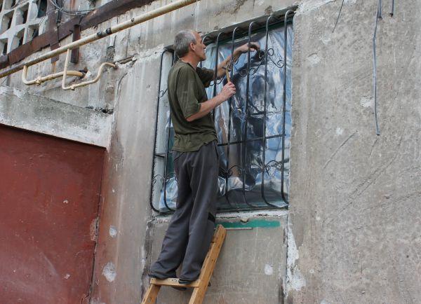 Житель Горловки закрывает окно полиэтиленовой пленкой в жилом многоквартирном доме, пострадавшем в результате обстрела города Горловки Донецкой области.