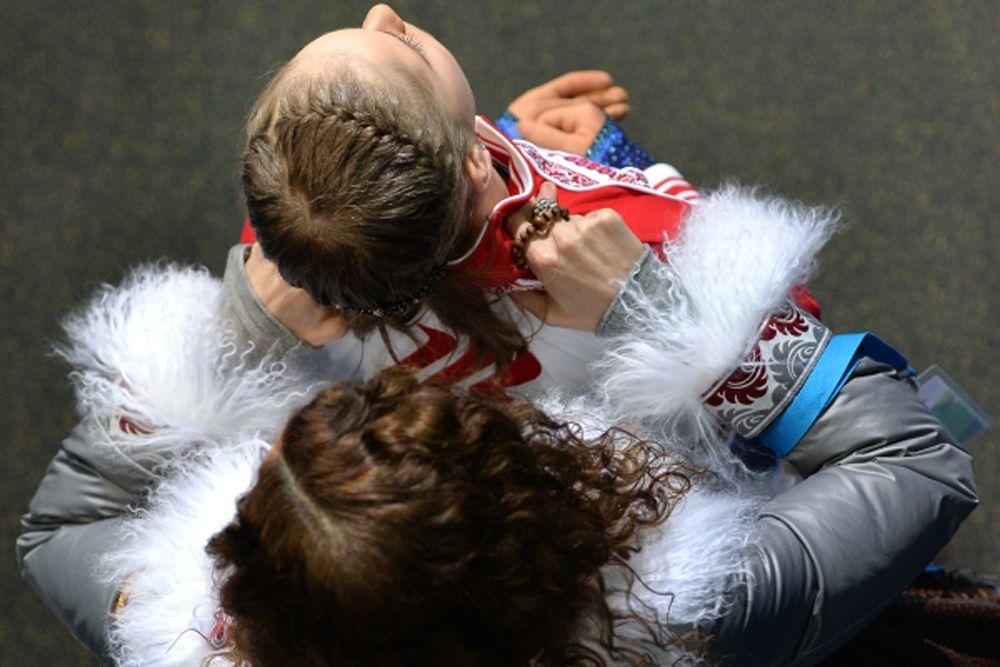 Юлия Липницкая (Россия) с тренером Этери Тутберидзе перед выступлением в короткой программе женского одиночного катания на соревнованиях по фигурному катанию на XXII зимних Олимпийских играх в Сочи. 2014 год.