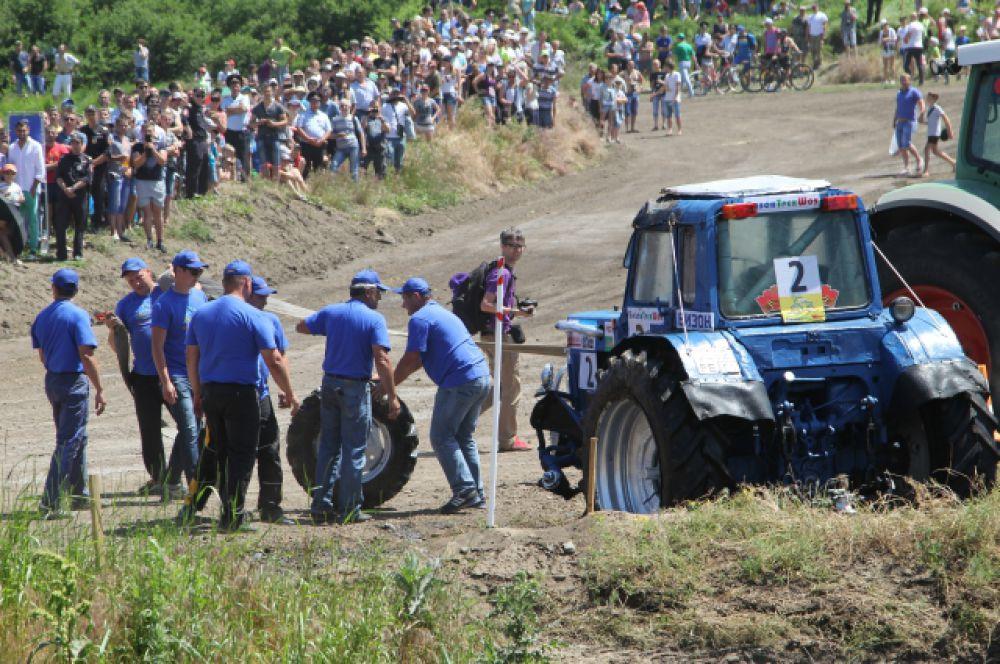 Мало того, что трактор пилота под номером 2 перевернулся, так у машины ещё оторвало колесо. Механизатор бросает шлемом в отчаянии по трактору. Для него гонка закончена.