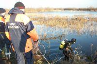 Аквалангист спускается в озеро чистить трубу, которую забили травой и ветками бобры.