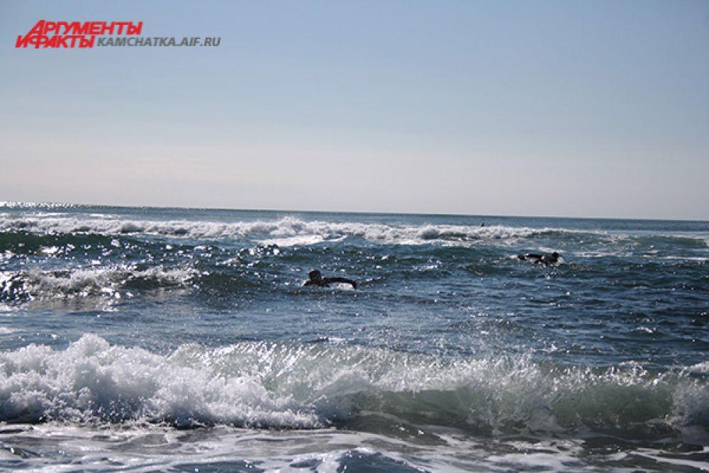 Огромные волны сбивают спортсменов с доски.