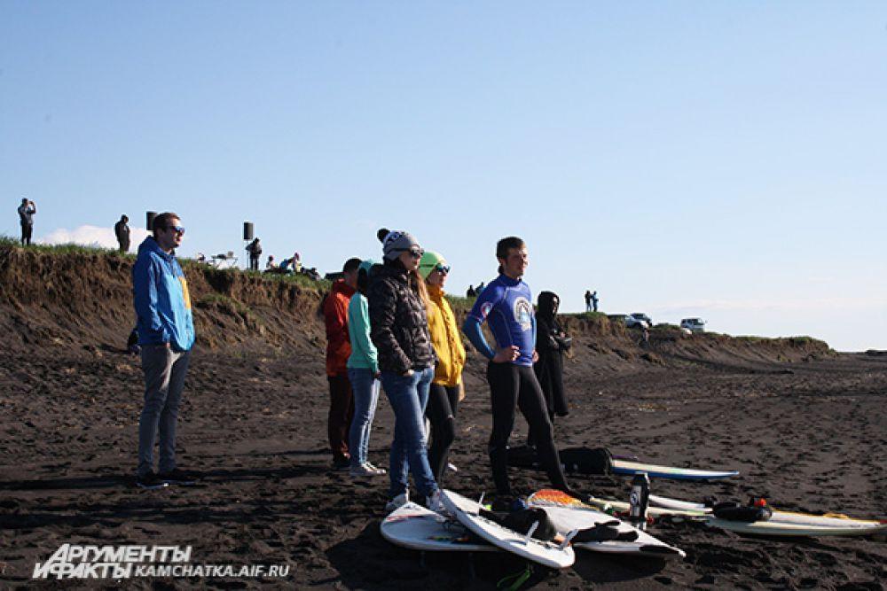 Зрители и сёрферы поддерживают участников заплыва с берега.