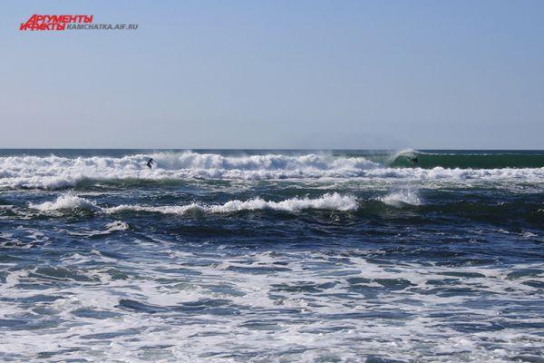 Спортсмены ловят волну далеко от берега.