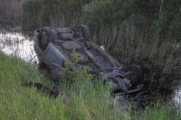 Машина упала в полный воды кювет и опрокинулась.