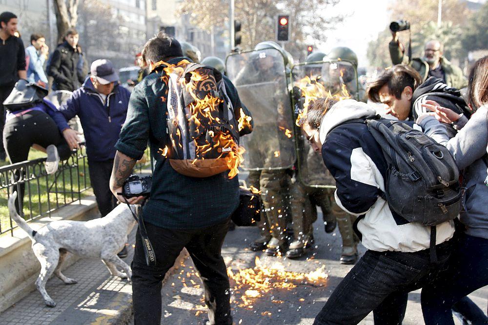 18 июня. Протестующие студенты, охваченные пламенем в Чили.