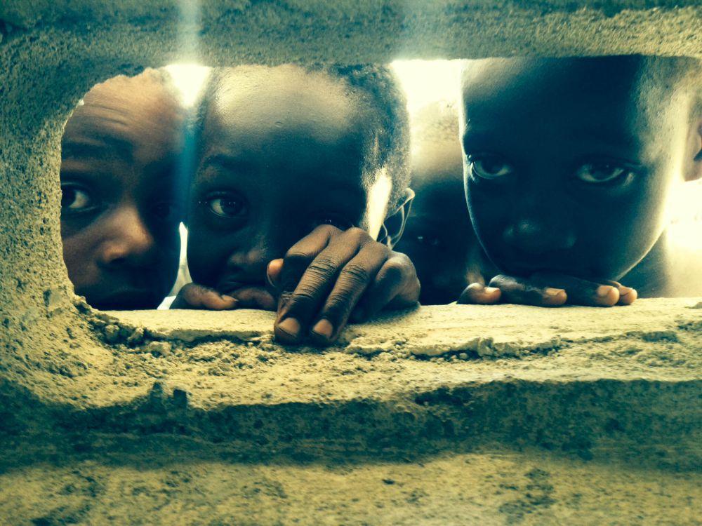 1-е место в номинации «Дети» досталось Джереми Керну из США. Джереми работает врачом в детском медицинском центре Вашингтона. «Это фото было сделано во время третьей поездки на Гаити, — рассказывает автор снимка. — В этот день мы остановились около школы, построенной из шлакобетонных блоков. Отверстия в них служили детям окнами, через которые проникал свет и осуществлялась вентиляция. Обычно в школах они проводят целый день. Их очень заинтересовали команды иностранных врачей, за которыми они наблюдали из этих окон».