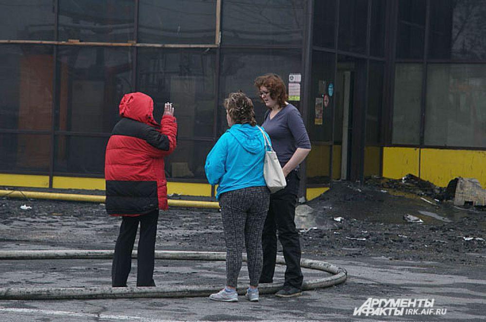 Работники магазинов, работавших в ТЦ утром собрались к месту пожара.