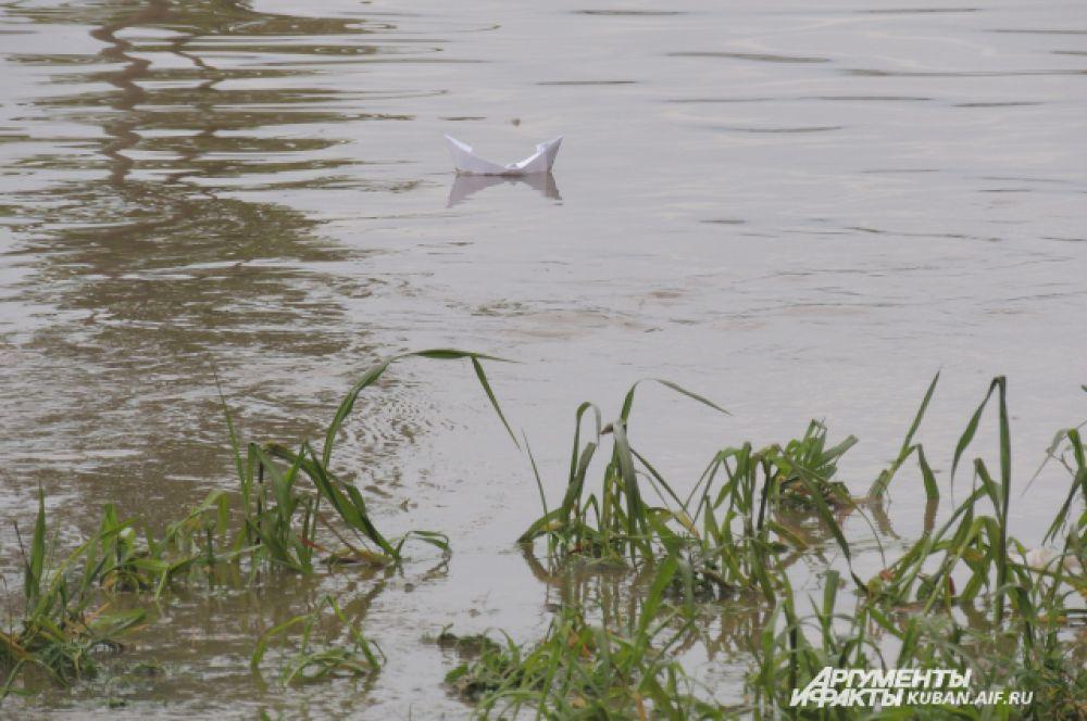 Кто-то пошутил и пустил по воде плыть бумажный кораблик.