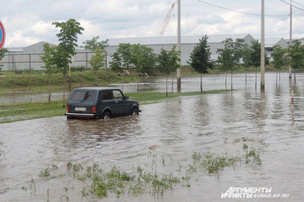 Водитель не отчаялся и решить переехать подтопленные места на дороге.