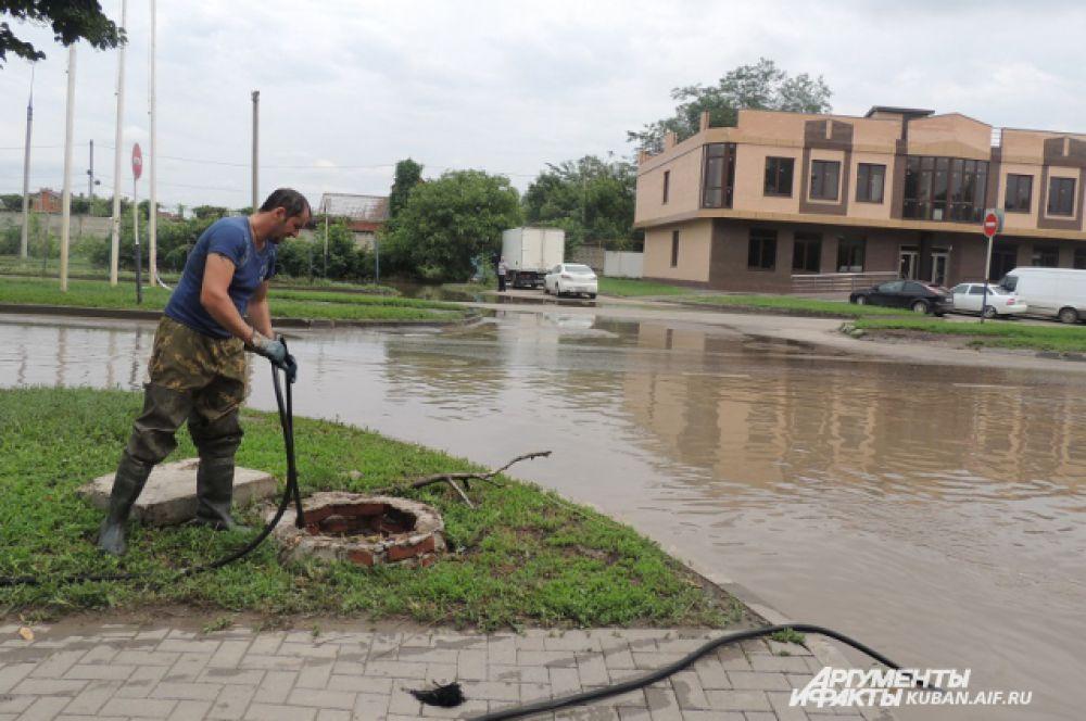 На улице неприятно пахнет фекалиями – рабочие решают и эту проблему, прочищая канализационные люки.