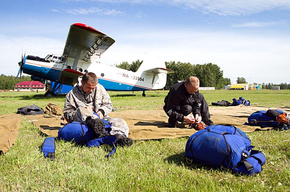 Эти храбрые ребята готовятся к прыжку, сидя на лётном поле. Перед посадкой в самолёт они должны удостовериться, что всё снаряжение в порядке.