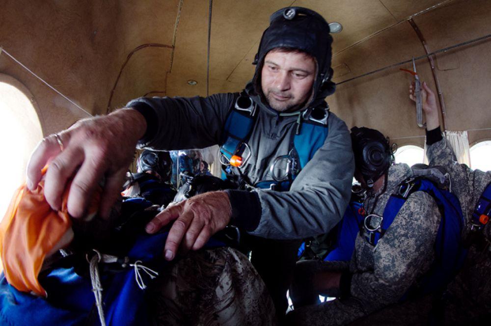 Перед прыжком парашютисты ещё раз проверяют, что всё готово.