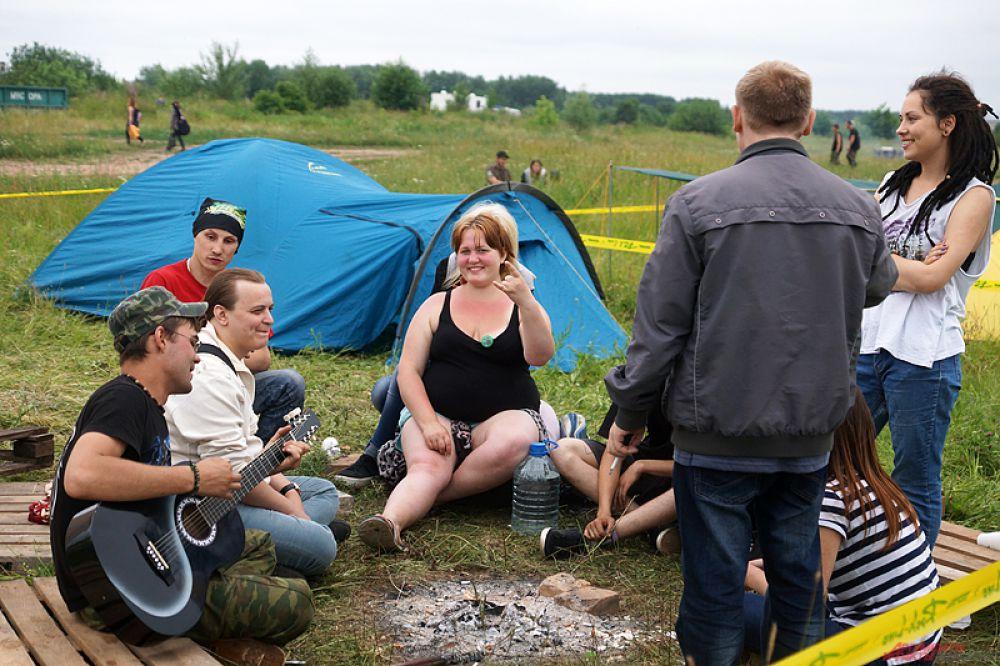 Участники играют на гитаре прямо около своих палаток.