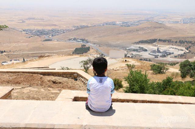 Езидский мальчик смотрит на долину, где когда-то располагались уничтоженные ныне деревни его предков.