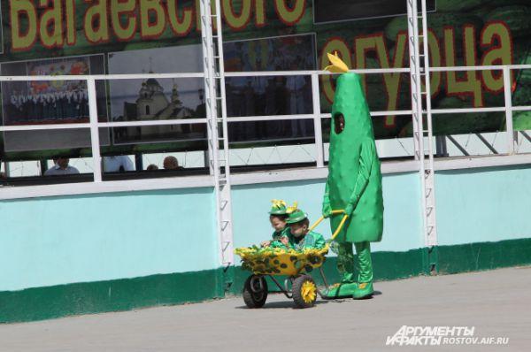 Главный герой дня - огурец, в нынешнем году выступает в образе ростовой куклы вместе с двумя маленькими огурчиками.