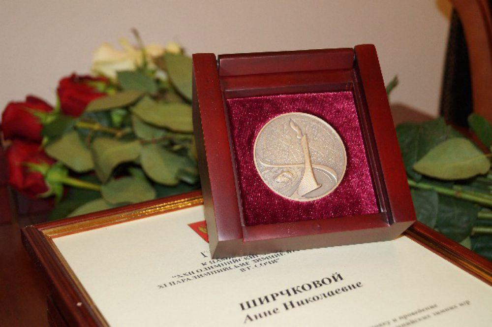 На одной стороне медали - олимпийский огонь, на второй - сочинские горы