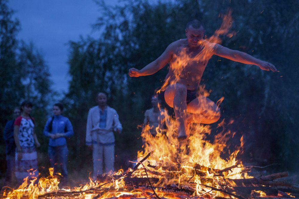 Россия, 9 июля. Мужчина прыгает через костер во время празднования Ивана Купала под Омском.
