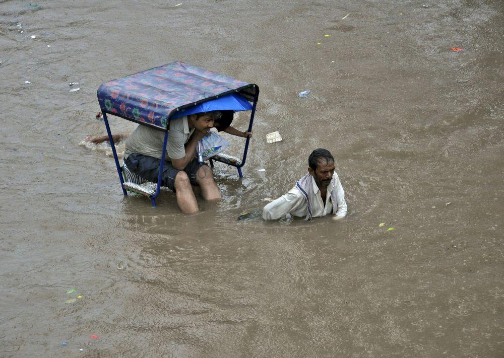 Индия, 10 июля. Рикша перевозит пассажира по затопленной дороге после ливневых дождей в Матхура.